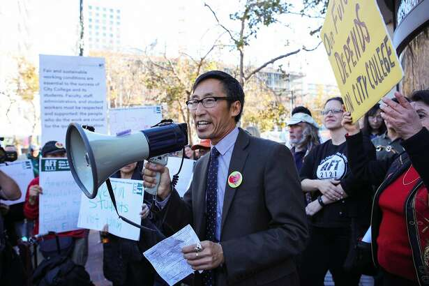Supervisor Eric Mar (center) speaks to a crowd of students and educators during a protest opposing CCSF's new budget cuts at UN Plaza in San Francisco, California on Thursday, November 12, 2015.