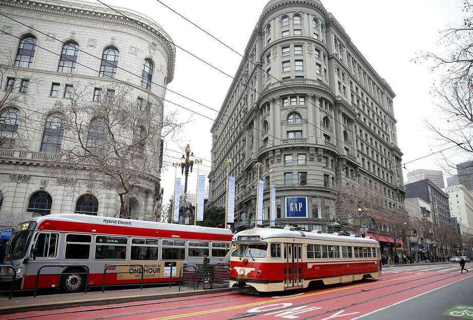 A Muni bus and streetcar pass in front of Gap on Market Street in San Francisco, California, on Wednesday, Dec. 30, 2015. Beginning April 23, Muni will launch changes on 18 lines, mostly increasing frequency but also add two new Owl lines. Photo: Connor Radnovich Connor Radnovich, The Chronicle