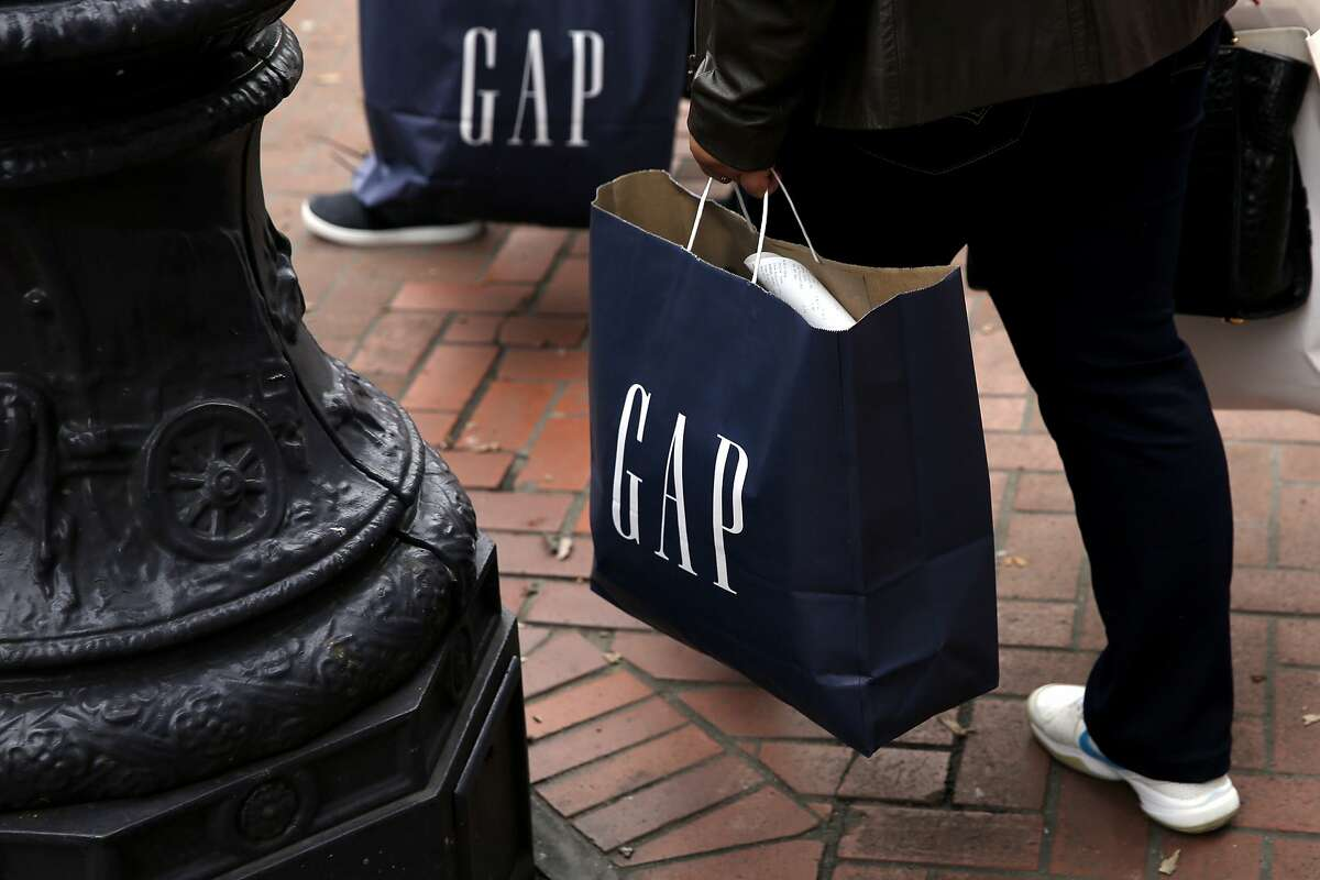 Shoppers carry Gap bags after exiting the store on Market Street in San Francisco, California, on Wednesday, Dec. 30, 2015.