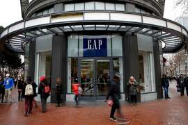Shoppers walk past Gap on Market Street in San Francisco, California, on Wednesday, Dec. 30, 2015.