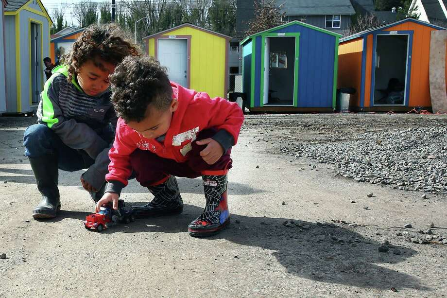 Five-year-old Tui and 2-year-old Sean play with toys at the new Othello Village homeless camp off of Martin Luther King Jr. Way in South Seattle, Tuesday, March 8, 2016. Both their families, and one other family, lived at Tent City 3 before moving into tiny houses at the new Othello camp on opening day. Photo: GENNA MARTIN, SEATTLEPI.COM / SEATTLEPI.COM