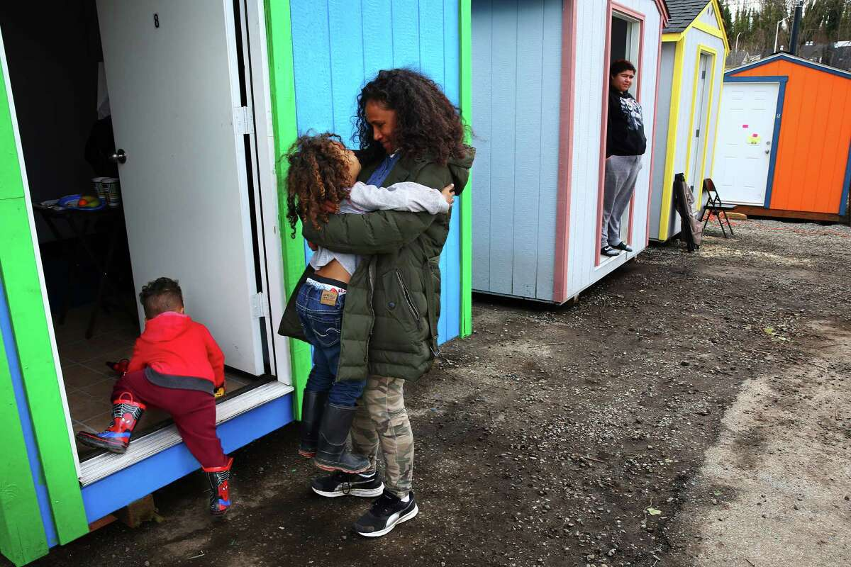 Seleima Silikula hugs her son Tui, 5, as they move into a new tiny house on opening day of the Othello Village homeless camp off of Martin Luther King, Jr. Way in South Seattle, Tuesday, March 8, 2016. Three families were among the first to move into the new camp. Othello Village will eventually include 16 tiny houses and 22 tents on platforms with room for 60-80 people.