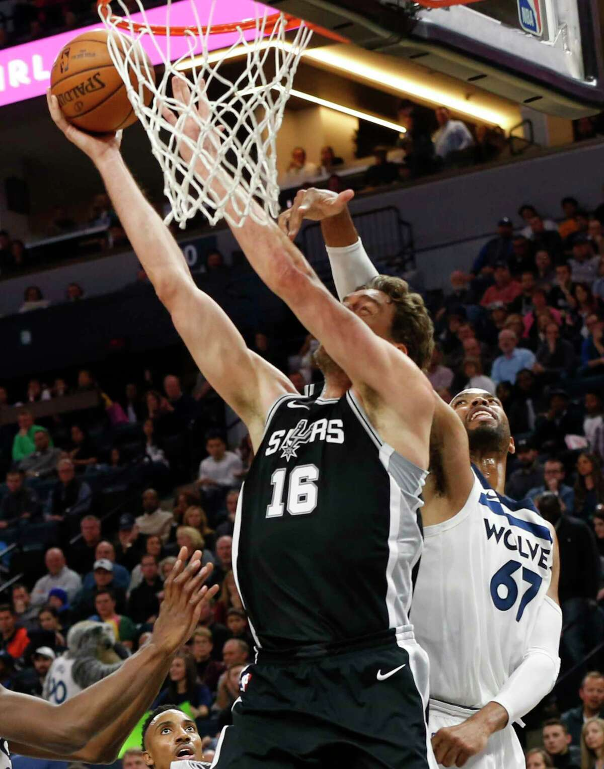 San Antonio Spurs' Pau Gasol, left, of Spain, is fouled by Minnesota Timberwolves' Taj Gibson during the first half of an NBA basketball game Wednesday, Nov. 15, 2017 in Minneapolis. (AP Photo/Jim Mone)
