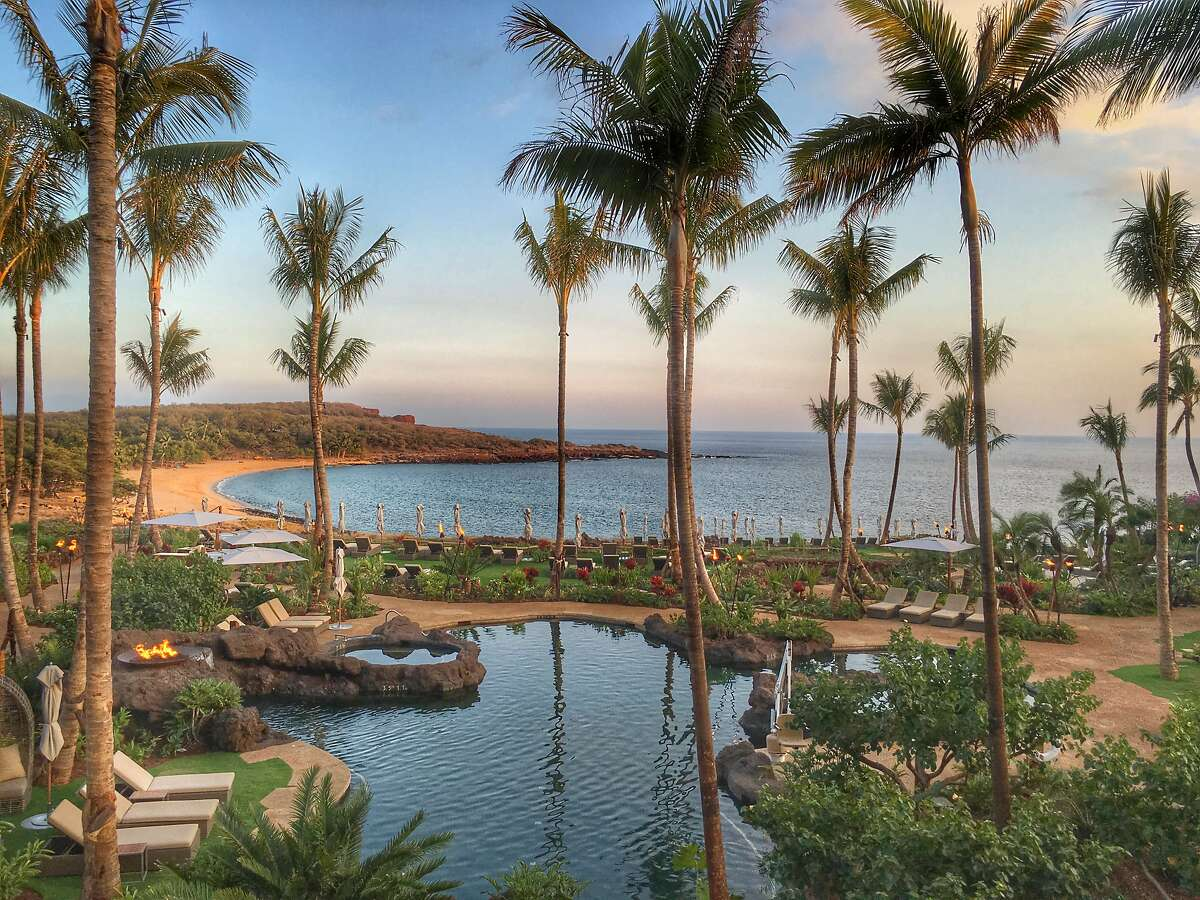The new pool area of Four Seasons Resort Lanai, overlooking Hulupoe Beach and Puu Pehe (Sweetheart Rock) in the distance, includes an adults-only area and lush landscaping. Credit: Ian Hersey / Special to The Chronicle
