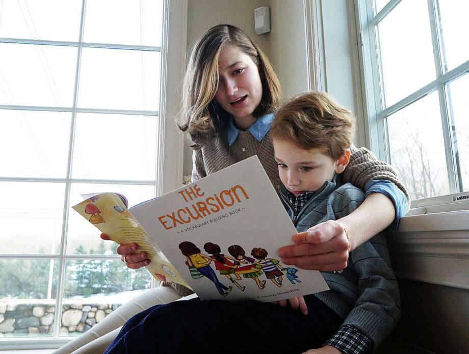 """Lauren Telesz, 18, reads her new children's book, """"The Excursion,"""" to her brother, Grant, 5, at their Mine Hill Road home. Photo: Genevieve Reilly /Hearst Connecticut Media / Fairfield Citizen"""