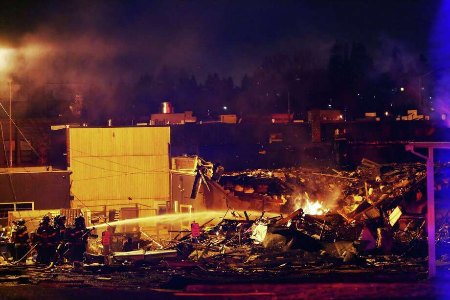 Seattle firefighters work to put out flames at the scene of a gas explosion near the intersection of Greenwood Avenue North and 85th Avenue North in Greenwood that occurred early Wednesday morning, March 9, 2016.  At least two commercial buildings were leveled. Photo: GENNA MARTIN, SEATTLEPI.COM / SEATTLEPI.COM