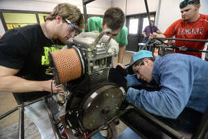 Lamar University engineering students, including (from left) Ryan Fischer, Beau Tallarita, and Dustin Berry, position the engine as work continues on their entry for next month's Shell Eco-marathon Americas 2016 in Detroit. They are nearing the deadline for their high fuel efficiency car, which will compete against several others at the national event. In all, twelve students are involved with the project, and have been working numerous hours each week building the chassis, welding, bolting and tweaking their design for optimal efficiency. April 23, they will compete, making 10 laps on a 3/4 mile track on less than 16 oz. of diesel fuel. The group raised $10, 000 to build the car, getting money from corporate sponsors as well as donations through a GoFundMe account. Photo taken Friday, March 4, 2016 Kim Brent/The Enterprise