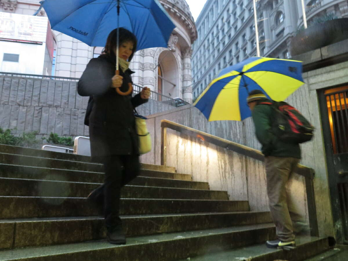 Pedestrians commute to work under a light rainfall in San Francisco on Wednesday March 9, 2016.