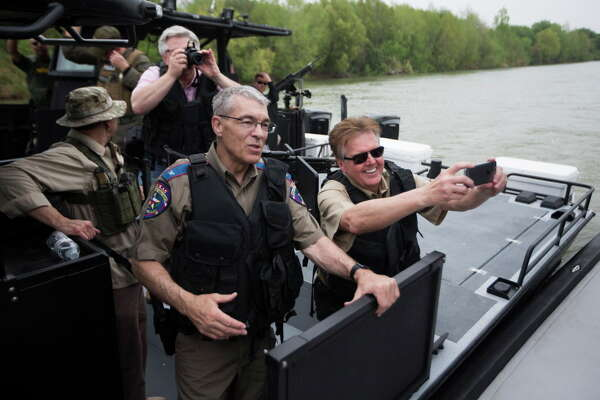 Lieutenant Governor Dan Patrick, right, accompanied by the director of the Texas Department of Public Safety Steven McCraw, left, takes photos during a ride on a super shallow waters boat recently acquired by DPS with Texas state funds. Patrick spent Tuesday taking a look at the border security improvements as well as speaking with the different law enforcement agencies working on the border.  Tuesday, March 8, 2016.