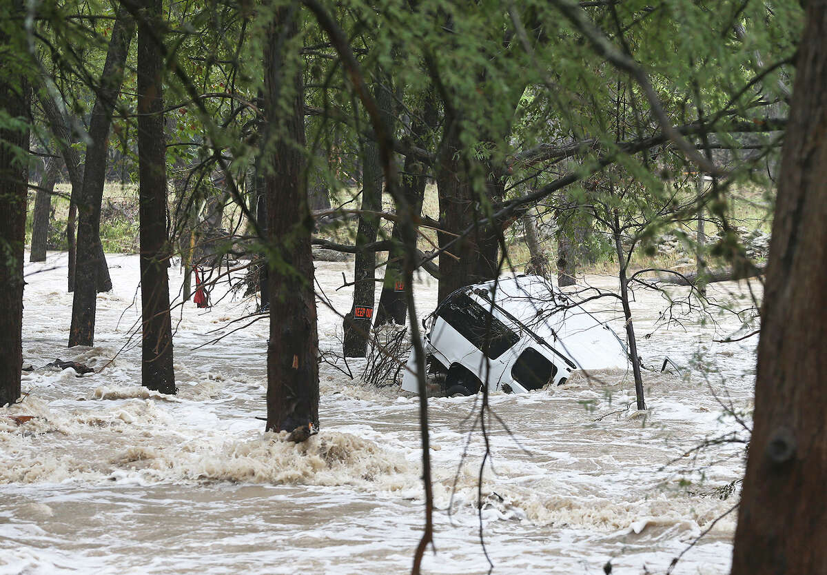 A SUV remains partially submerged off the Cypress Creek bridge in Wimberley during flooding in Comal and Hays counties on Oct. 30. It was the second time Wimberley was severely flooded last year.
