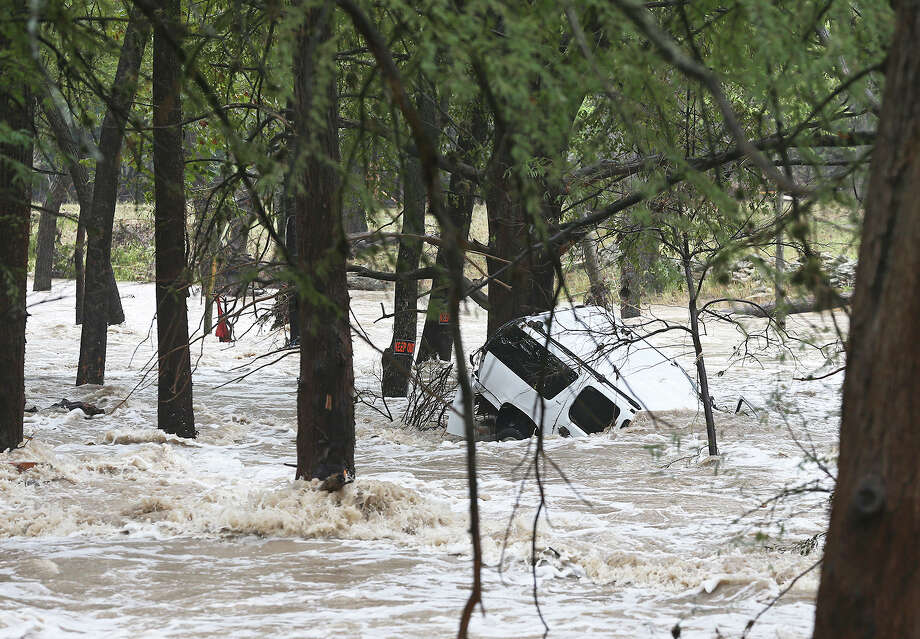 A SUV remains partially submerged off the Cypress Creek bridge in Wimberley during flooding in Comal and Hays counties on Oct. 30. It was the second time Wimberley was severely flooded last year. Photo: Tom Reel /San Antonio Express-News