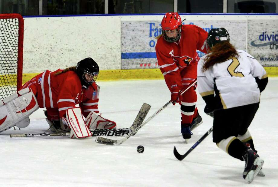 Greenwich's Reilly Van Duyne, center, rushes in to disrupt a drive to the goal by St. Joseph's Amelia Walker during girls hockey action on Feb. 3. Reaching to cover the puck is Greenwich goalie Jessie Aselin. Photo: Christian Abraham / Hearst Connecticut Media / Connecticut Post