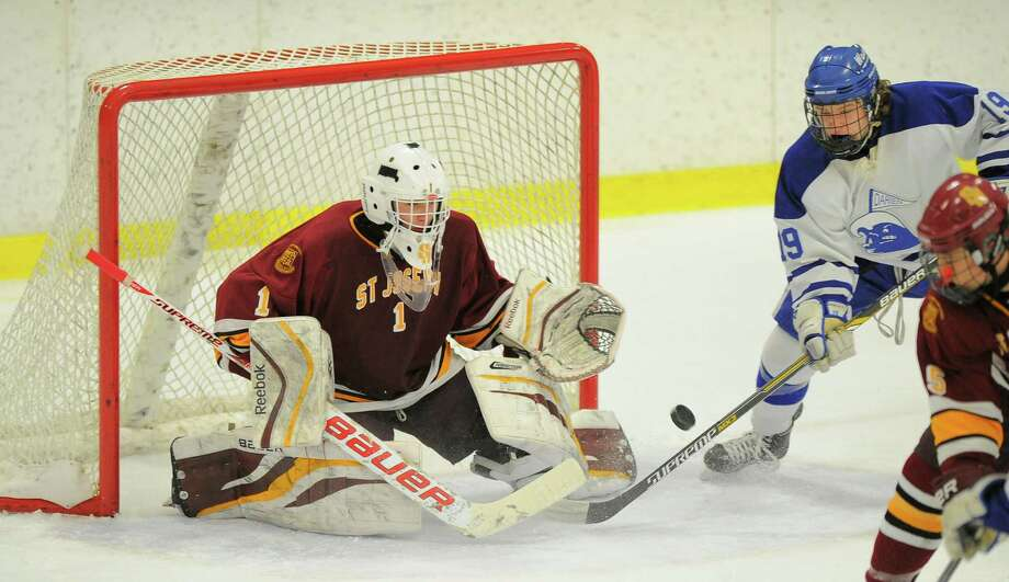 St Joseph goalie Ryan Wilson makes a save on s shot by Darien's Benjamin Brown Wednesday at Terry Conners Ice Rink in Stamford. Wilson made 43 saves to lead the Cadets to the upset win over the Blue Wave. Photo: Matthew Brown / Hearst Connecticut Media / Stamford Advocate
