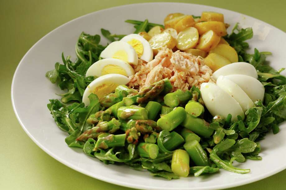 A spring version of the French classic Salade Nicoise subs asparagus spears for green beans and leaves out tomatoes. Plate it as a composed salad, arranging each ingredient atop a bed of dressed arugula. Photo: Craig Lee /Special To The San Francisco Chronicle / ONLINE_YES