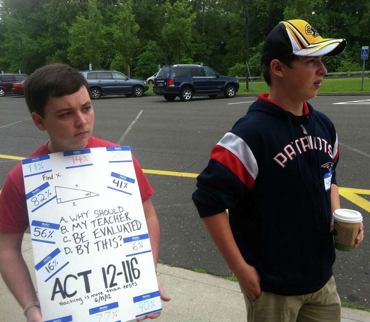 Staples High School juniors Ryan Shea, left, and Jacob Meisel participate in a protest outside the front entrance of the school related to teacher evaluation criteria in Connecticut's new education reform law. Monday, June 11, 2012/ Westport, CT
