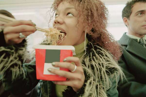 Young woman eating takeaway food on train, close-up
