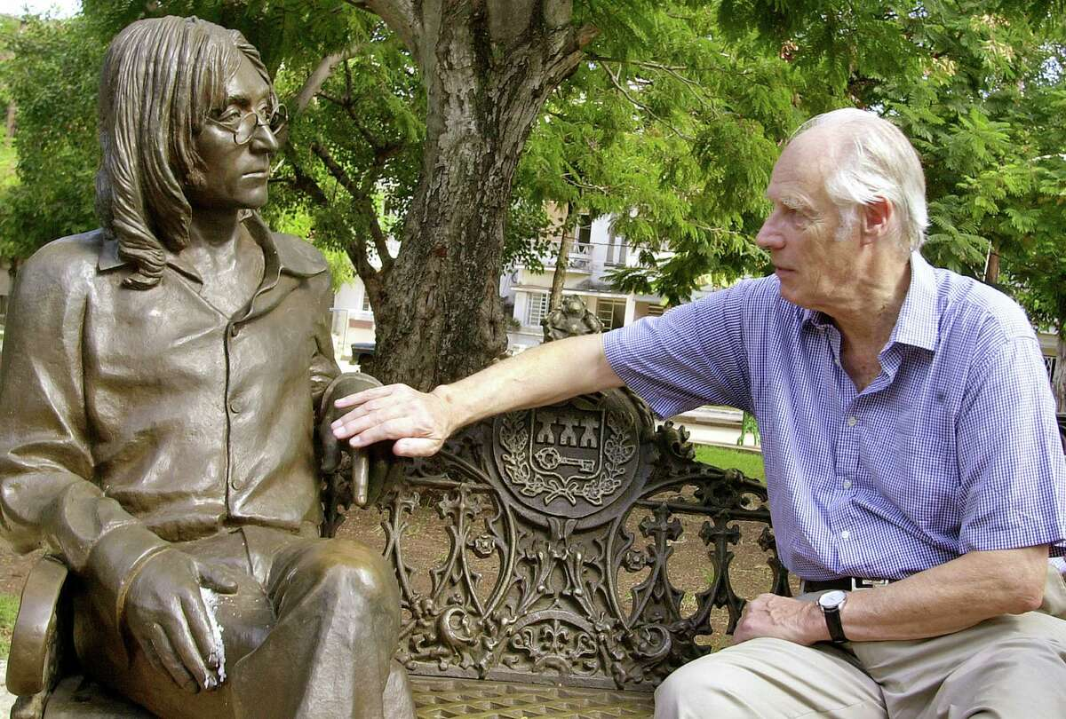 FILE - In this Oct. 30, 2002 file photo, Beatles producer George Martin touches a statue of John Lennon in a park in the Vedado neighborhood of Havana, during his visit to Cuba. (AP Photo/Cristobal Herrera, File) ORG XMIT: BKCD302