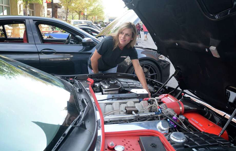 The Woodlands Car Club member Dana Pritchard adjusts a setting on her father's 2002 Corvette drag car that is on display during The Woodlands Car Club's Cars and Coffee for a Cause car show held first Sunday of each month at Market Street. Photo: David Hopper, Freelance / freelance