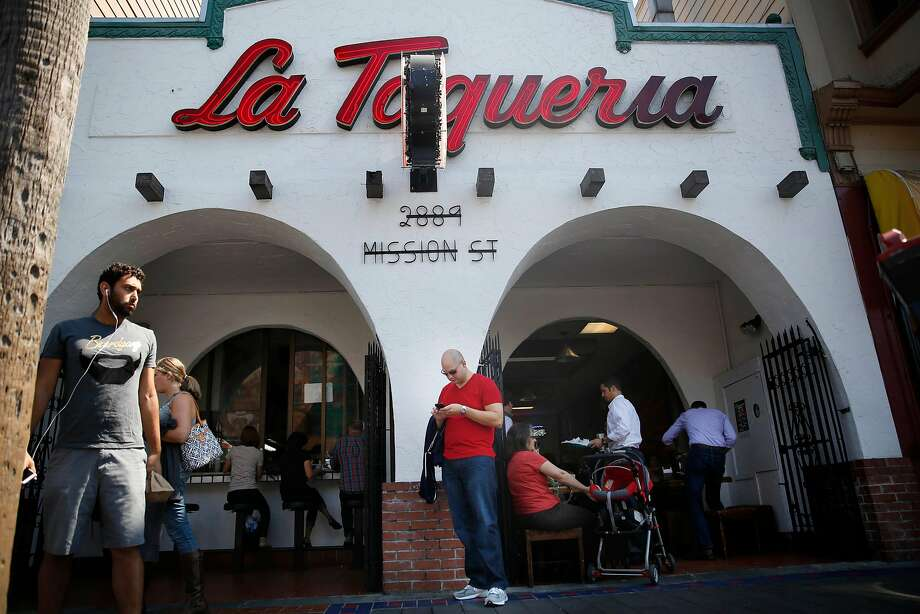 Matt Seiter , of Charlotte, North Carolin, checks his phone as he and his wife Courtney Seiter (partially seen second from left) leave La Taqueria on Wednesday, September 10,  2014 in San Francisco, Calif.  The Seiters had read the burrito review of Anna Maria Barry-Jester, FiveThirtyEight�s burrito correspondent, and came to La Taqueria to try the food. Photo: Lea Suzuki / The Chronicle