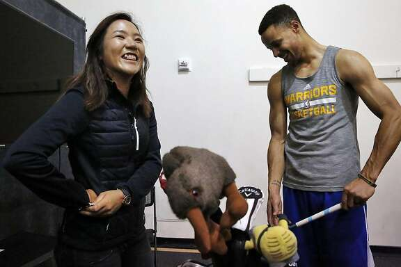 Professional golfer Lydia Ko jokes with Stephen Curry after the Warriors' practice at the Warriors Practice Facility in the Oakland Marriott City Center March 9, 2016 in Oakland, Calif.