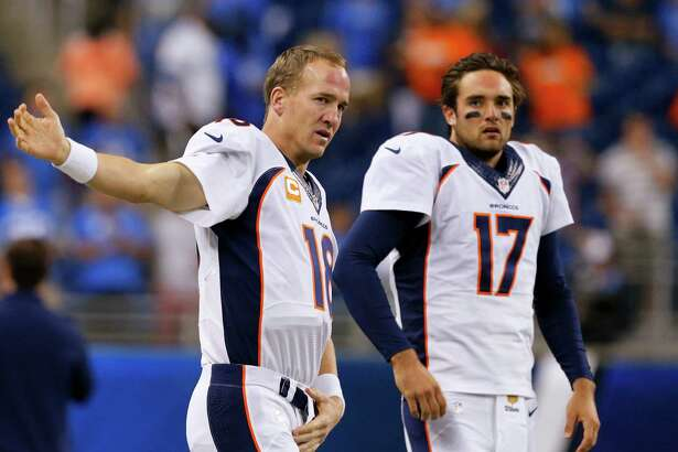 """FILE - In this Sept. 27, 2015, file photo, Denver Broncos quarterbacks Peyton Manning (18) and Brock Osweiler (17) get ready for the Broncos' NFL football game against the Detroit Lions in Detroit. Osweiler gets his first NFL start in his fourth pro season, on Sunday against the Chicago Bears. Manning promises not to """"be in his ear"""" all the time, but rest assured he will have some input. (AP Photo/Rick Osentoski, File)"""