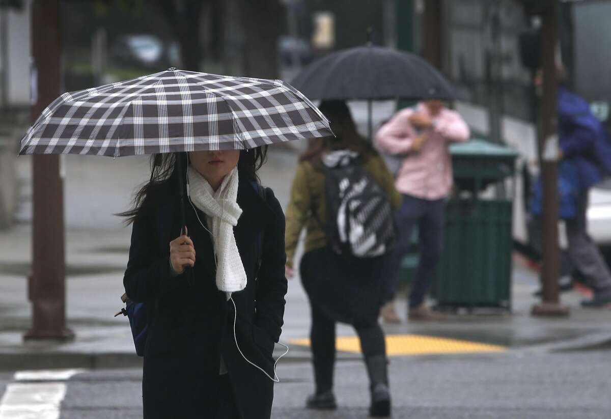 A woman carries an umbrella on Center Street during a light rain in Berkeley, Calif. on Wednesday, March 9, 2016.