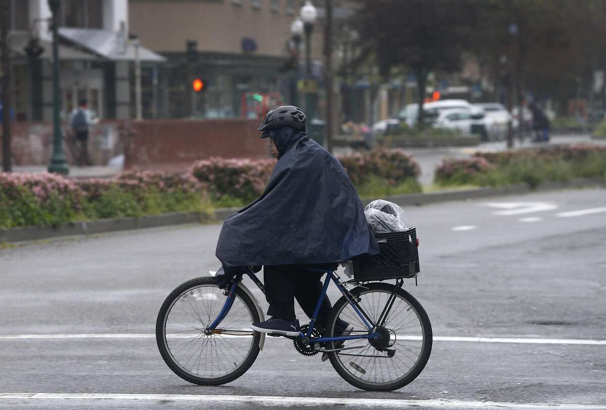 A bicyclist peddiles in the rain in downtown Berkeley, Calif. on Wednesday, March 9, 2016.