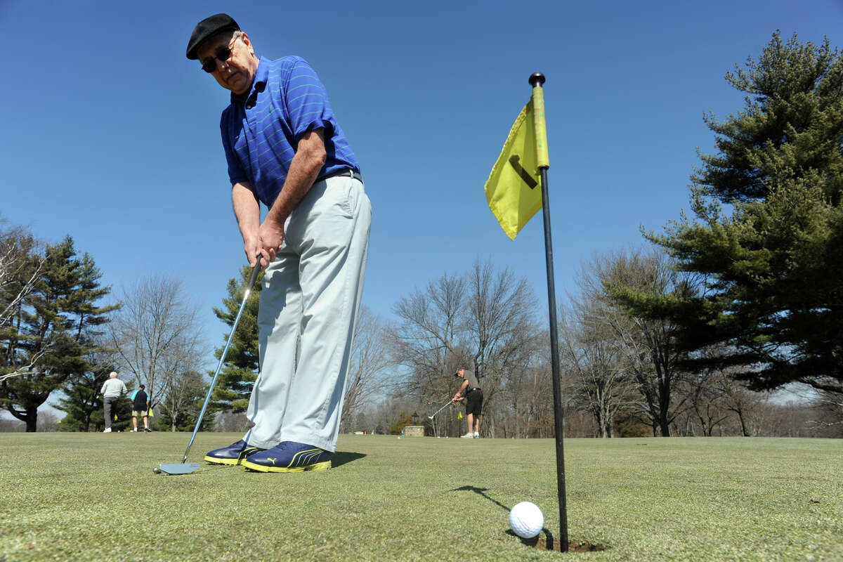 Ralph Iassogna, of Shelton, sinks a putt as he practices before his first round of golf of the season at Fairchild Wheeler Golf Course, in Fairfield, Conn. March 9, 2016.
