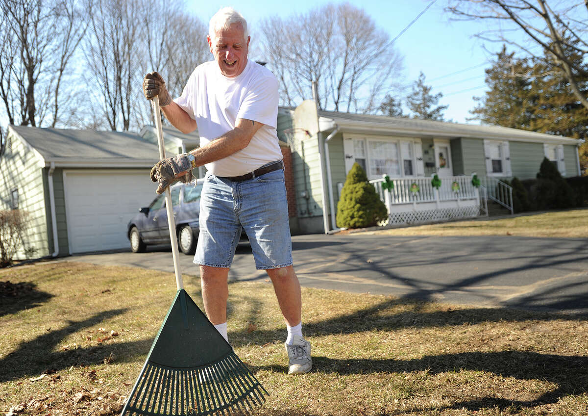 Ray Steinman takes advantage of the warm weather to rake up his yard in a tee shirt and shorts on Maplewood Avenue in Milford, Conn. on Wednesday, March 9, 2016.