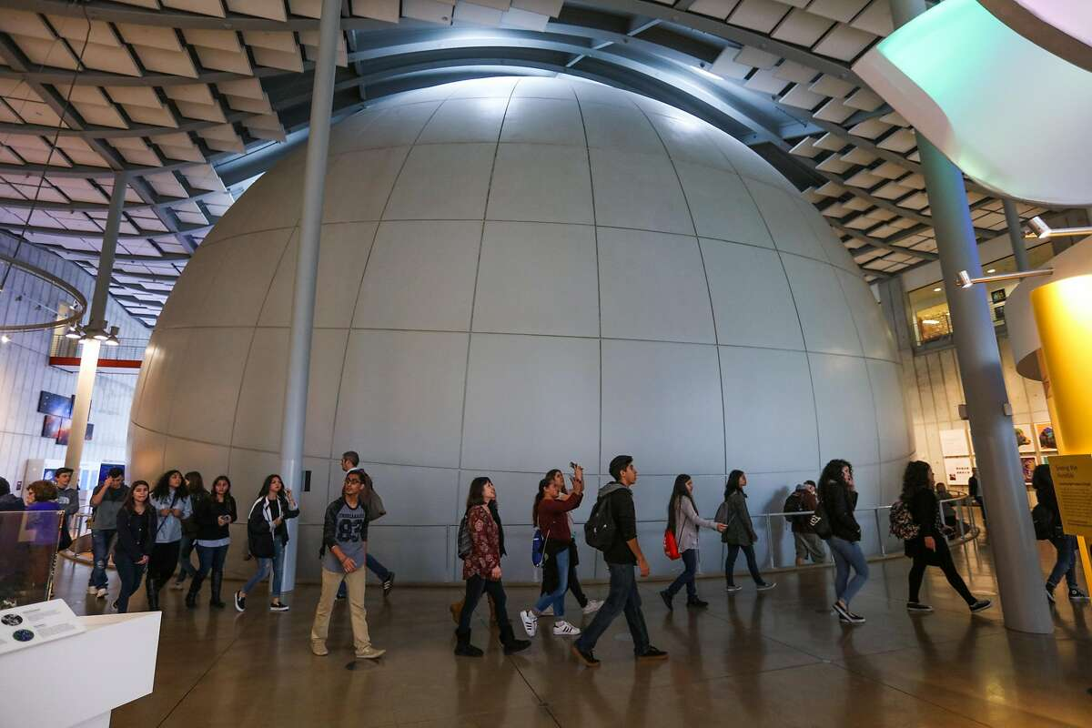 Visitors walk past the planetarium at the California Academy of Sciences, in San Francisco, California, on Wednesday, March 9, 2016.