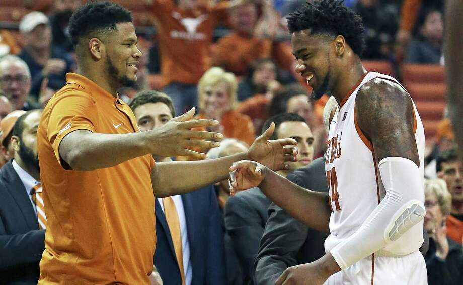 Injured center Cameron Ridley offers a hug to his replacement Prince Ibeh as he comes out of the game as Texas hosts TCU at the Erwin Center in Austin on Jan. 26, 2016. Photo: Tom Reel /San Antonio Express-News / 2016 SAN ANTONIO EXPRESS-NEWS