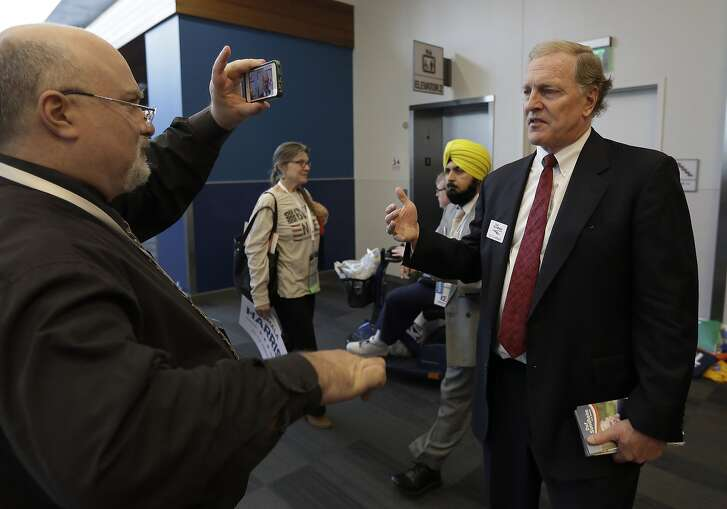Republican candidate for US Senate Duf Sundheim, right, has his photo taken at the entrance to the main hall of the California Democrats State Convention Saturday, Feb. 27, 2016, in San Jose, Calif. (AP Photo/Ben Margot)