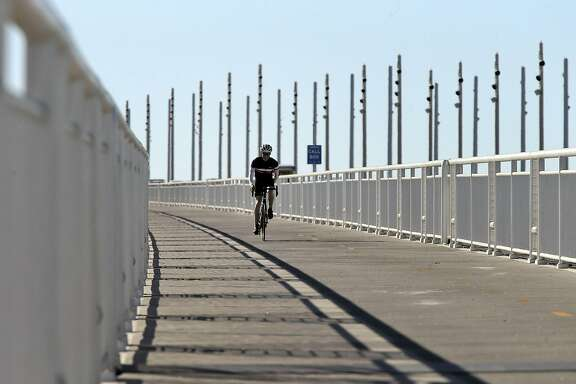 A cyclist makes his way down the Bicycle Pedestrian Path on the Bay Bridge in Oakland, Calif., on Thursday, October 29, 2015. The Bay Bridge bike path from Oakland to Treasure Island has been delayed yet again. Originally scheduled to open along with the new eastern span two years ago, completion had to wait for demolition of part of the old span, which was to be completed by summer. Then it was delayed until late fall/end of the year. Now, it looks like bike riders won't be able to pedal from the East Bay to Treasure Island until sometime next year.