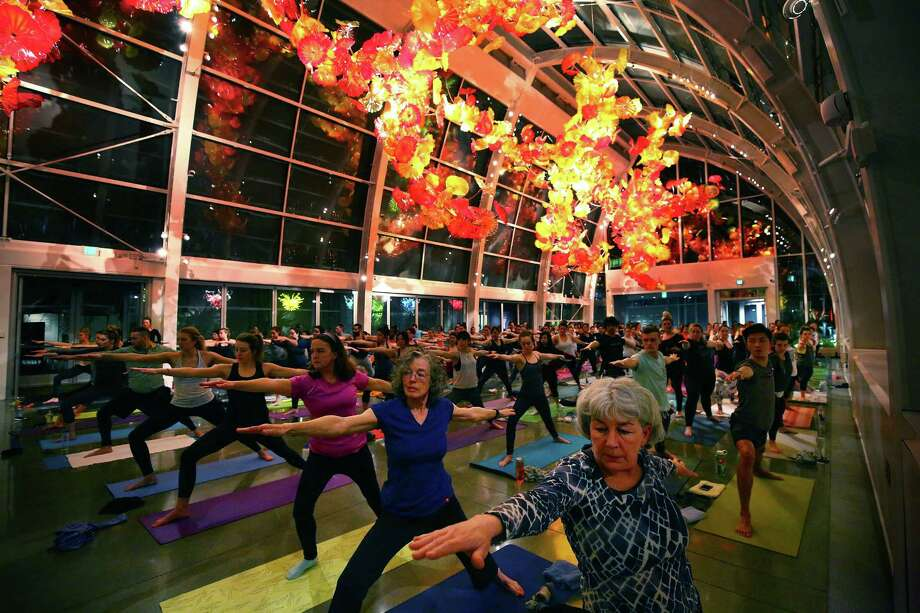 People participate in the Yoga Under Glass event at the Chihuly Garden and Glass, Tuesday evening, March 8, 2016. Core Power Yoga Studio instructors lead the class through a one hour session under the Chihuly art in the Glasshouse.  The museum hosts semi-frequent day time and night time yoga events. Photo: GENNA MARTIN, SEATTLEPI.COM / SEATTLEPI.COM