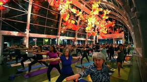 People participate in the Yoga Under Glass event at the Chihuly Garden and Glass, Tuesday evening, March 8, 2016. Core Power Yoga Studio instructors lead the class through a one hour session under the Chihuly art in the Glasshouse.  The museum hosts semi-frequent day time and night time yoga events.