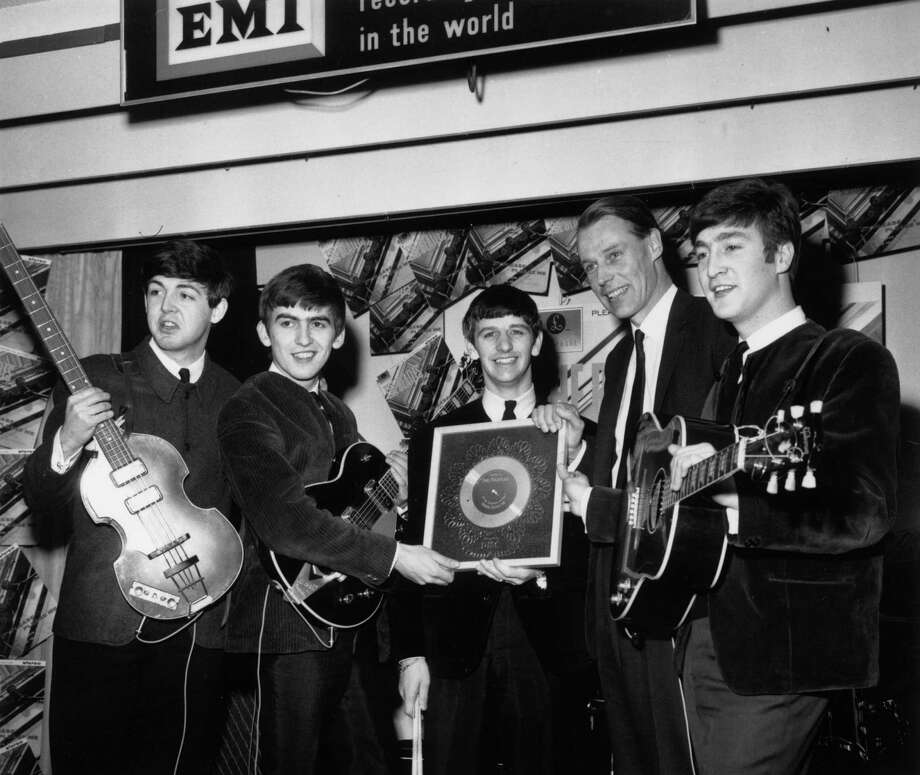 """George Martin (second from right) poses with the Beatles and their silver disc for """"Please, Please Me"""" in April 1963. Photo: Chris Ware / / Hulton Archive"""
