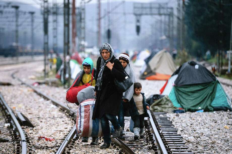 A woman and three children walk on railway tracks at the Greek-Macedonian border near Idomeni, where thousands of migrants are trapped by the Balkan border blockade. Photo: Dimitar Dilkoff / Getty Images / AFP or licensors