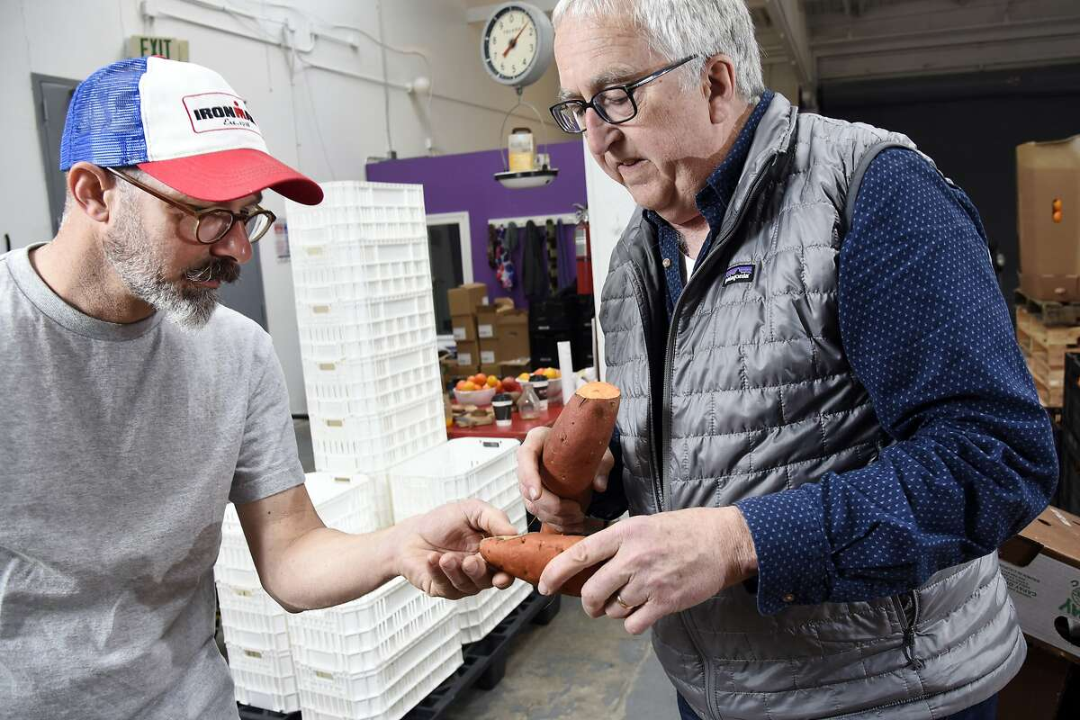 Founder and CSO Ron Clark, right, and warehouse manager Chad Wagner inspect a yam from a box that is set for donation to a local food bank, at Imperfect Produce's warehouse in Emeryville, CA, Wednesday March 9, 2016.