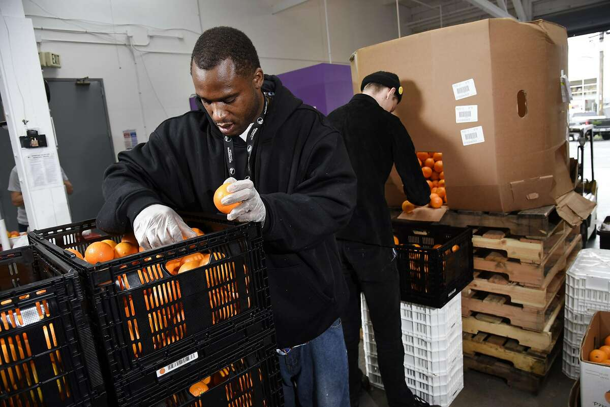 Operation assistants Jonel Jimmerson, left, and Dallin Kapp sort through oranges that are bought as waste from growers and are then divided up according to their saleability at Imperfect Produce's warehouse in Emeryville.