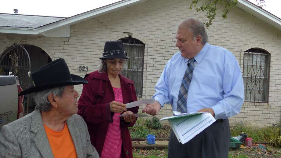 Tax Assessor- Collector Albert Uresti presents property tax refunds to Rogelio and Rachel Chapa. Uresti discovered the couple had lost their homestead and over-65 exemptions inadvertently while he was campaigning for re-election in January. Photo: John W. Gonzalez /San Antonio Express-News
