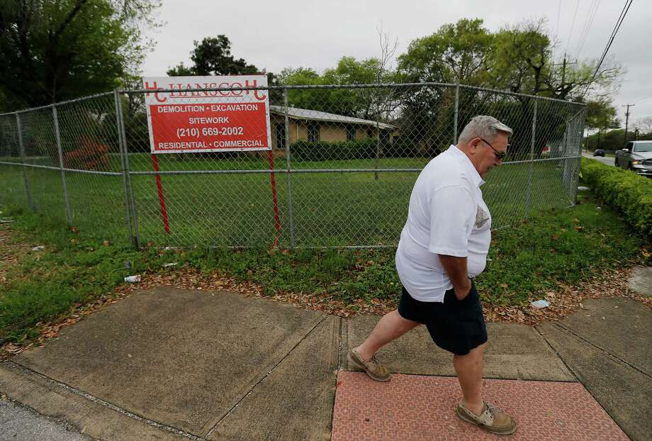 """Shearer Hills homeowner Tom Seaman walks past a fenced property that is owned by the Oblate School of Theology near Oblate and Shearer Hills Drive on Wednesday, Mar. 9, 2016. Seaman and other members of the North Shearer Hills Homeowners Association have expressed their dissatisfaction with the fact that The Oblate School of Theology will be demolishing four existing homes and building several new ones in their neighborhood. The group voiced several concerns and are upset with the Oblate's """"shroud of secrecy"""" behind the proposed construction in the neighborhood across from the school. (Kin Man Hui/San Antonio Express-News) Photo: Kin Man Hui, Staff / San Antonio Express-News / ©2016 San Antonio Express-News"""