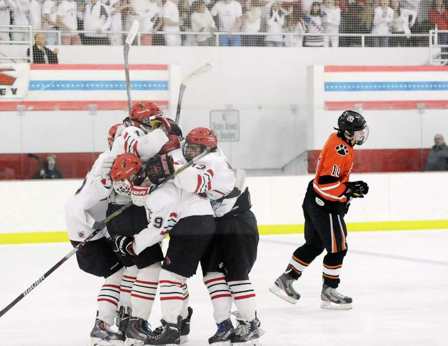 As Ridgefield's Pete Sarath skates away, a group of Greenwich players including Ollie Fulton (9) and KC Cunningham (13) celebrate a Mike Mozian goal Wednesday at Hamill Rink in Greenwich. Photo: Bob Luckey Jr. / Hearst Connecticut Media / Greenwich Time