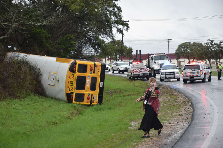 Two adults were injured Wednesday morning when a Boerne Independent School District bus bound for Champion High School hit a wet stretch of pavement and flipped on its side. Photo: Mark D. Wilson / San Antonio Express-News