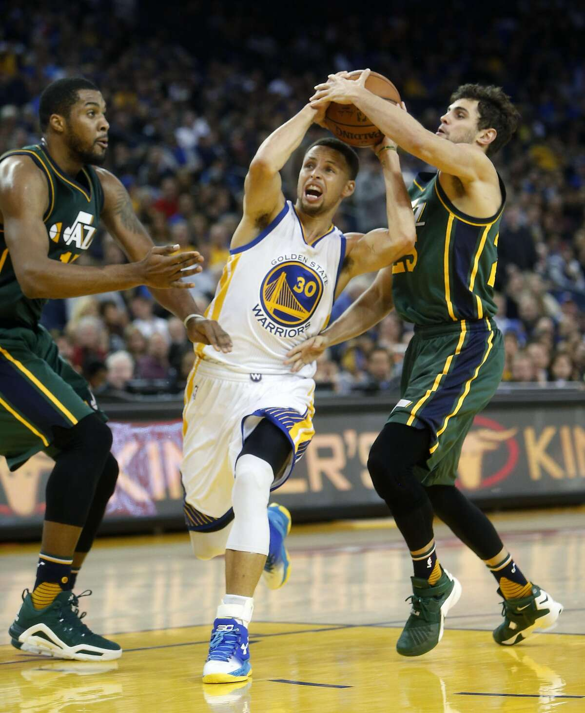 Golden State Warriors' Stephen Curry is defended by Utah Jazz' Raul Neto in 3rd quarter during NBA game at Oracle Arena in Oakland, Calif., on Wednesday, March 9, 2016.