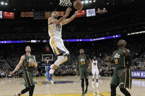 Stephen Curry (30) splits the defenders and comes in for a layup in the second half as the Golden State Warriors played the Utah Jazz at Oracle Arena in Oakland, Calif., on Wednesday, March 9, 2016.