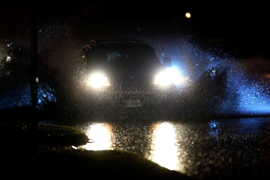 Water splashes in the air as a motorist drives through the flooded roadway on Martin Luther King Jr. Parkway near Washington Boulevard on Wednesday night. MLK Parkway was closed heading through Lamar University's campus due to flooding between Lavaca Street and Provost Umphrey Stadium.  Photo taken Wednesday 3/9/16 Ryan Pelham/The Enterprise Photo: Ryan Pelham / ©2016 The Beaumont Enterprise/Ryan Pelham