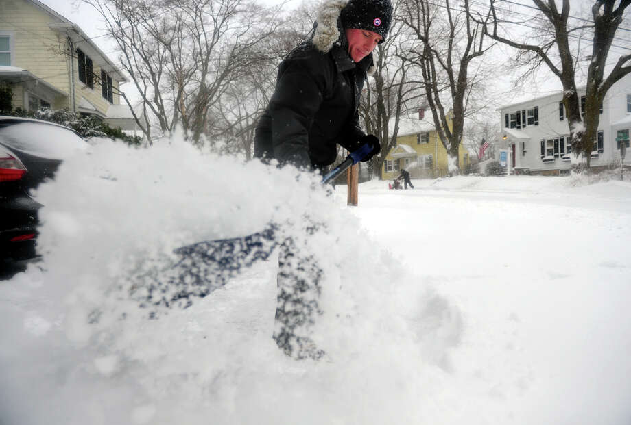 Mike Midgley shovels snow at his home on Colony Drive in Fairfield on Saturday Jan. 23, 2016. A nor'easter brought blizzard conditions into southwest Connecticut. It was the biggest snowfall during the 2015-16 winter. The National Oceanic and Atmospheric Administration said the 2015-16 winter was the warmest on record across the United States. Connecticut's winter temperatures were 7.7 degrees above normal. Photo: Christian Abraham / Hearst Connecticut Media / Connecticut Post