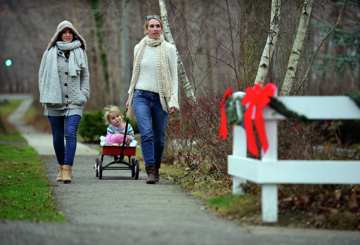 Shelly McDonald, of Milford, pulls her daughter Amelia, 3, along in a wagon as she walks with her sister Jill, on Edgefield Avenue in Milford, Conn. on Saturday Dec. 26, 2015. Connecticut say its warmest Christmas on record when the temperature soared to 64 degrees.