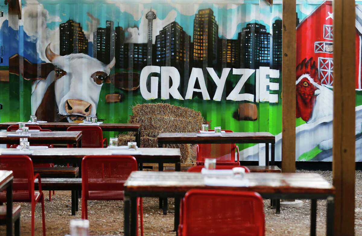 The rear patio offers plenty of seating and a fun farm-inspired mural, complete with bales of hay.