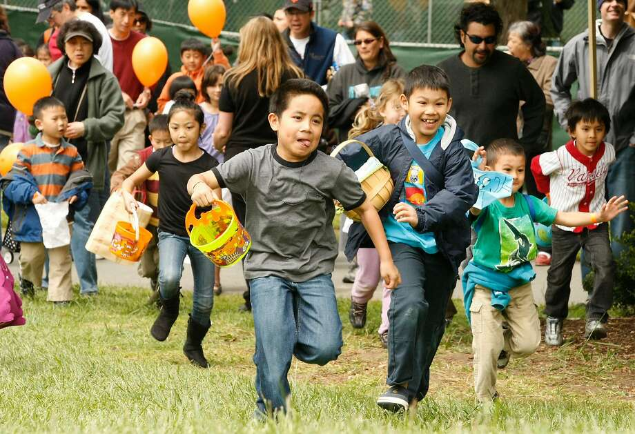 Children sprint to be the first to find Easter eggs at a Spring Eggstravaganza in Golden Gate Park. Photo: Alex Washburn, The Chronicle